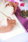 pink notebook and a feather pen on a wedding guest table