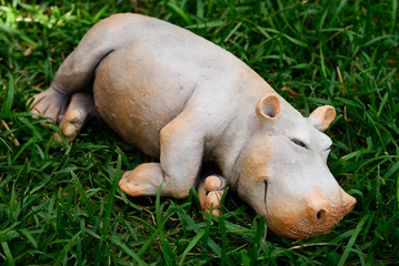 Small clay hippopotamus laying over green grass