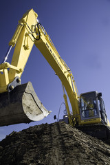 Yellow Excavator working soil on construction with deep blue sky