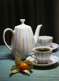 Two cups and a teapot on a green wooden napkin poster