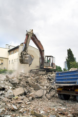 Cleaning ruins of building with bulldozer