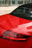 Red convertible car with building in background poster