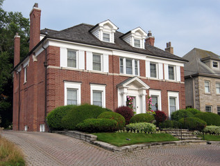 Large brick two storey home with white shutters