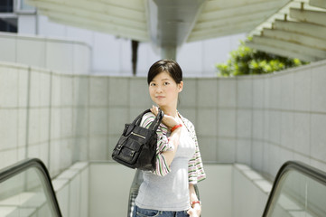 asian girl with handbag outdoors
