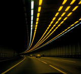 cars on road in tunnel with lights overhead poster