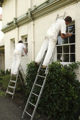 Two painters decorating the exterior of a house
