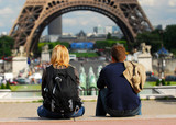 Young tourist couple sitting in front of Eiffel tower  poster