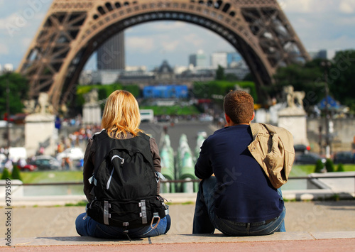 Leinwanddruck Bild Young tourist couple sitting in front of Eiffel tower