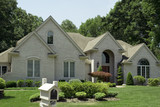Beautiful beige brick home with nice landscaping. poster
