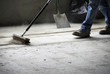 Construction worker sweeping up - 3796129