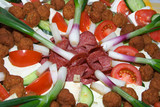 Arrangement of salami, rissole, bacon, cheese and vegetables poster