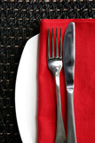 Place setting ~ knife and fork on red napkin and white plate poster