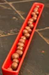 Red plate full of mini chocolate crunchy honeycomb balls