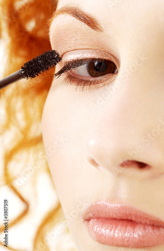 picture of lovely redhead applying black mascara