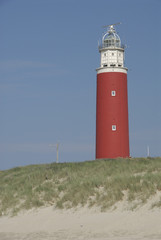red lighthouse on the beach on texel (the netherlands)