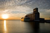 Old ship and grain elevator at sunset poster