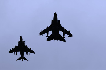 A silhouette jet fighters against a blue sky