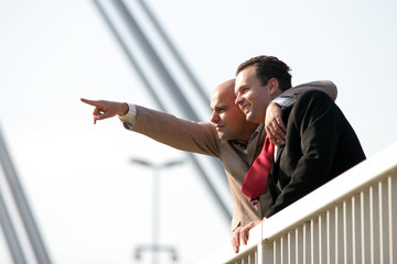 Two businessmen standing on bridge