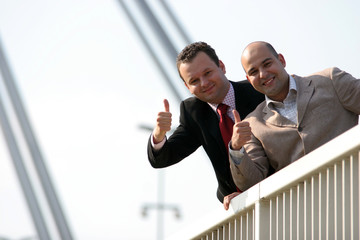 Businessmen standing on bridge and holding thumbs up