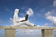 Woman working with is laptop with a beautiful blue sky