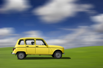 Yellow classic car at high speed in a green meadow
