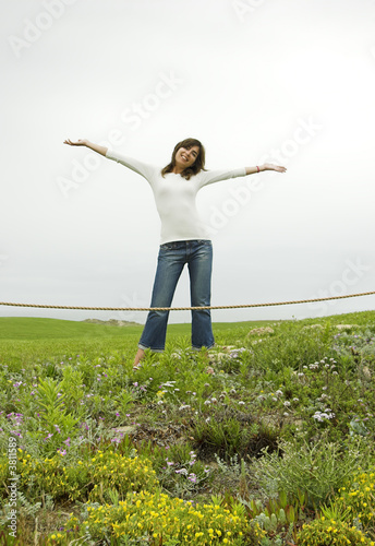 Happy woman with opean arms on a green landscape
