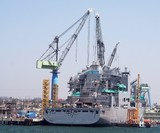A military ship docked in the shipyard getting upgraded poster