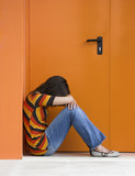 Loneliness woman on a orange door with hands over the knees poster