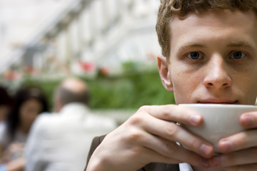 The young man drinking coffee in cafe