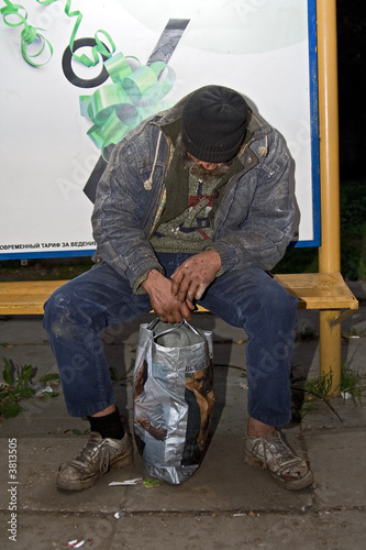 The drunk homeless the tramp fallen asleep at a bus stop