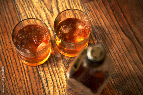 Two glasses from whisky and a bottle on a wooden table