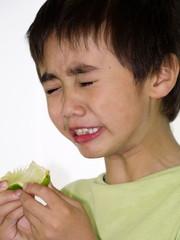 junge beißt in eine saure Limone