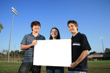 Three young friends holding blank white billboard outdoors poster