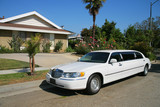 Fototapety White limousine next to a residential house