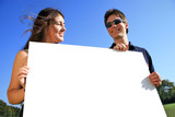 Young couple holding a blank white billboard outdoors poster