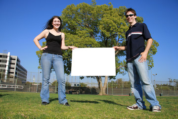 Young couple holding a blank white sign outdoors