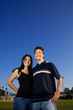 Smiling young couple embracing outdoors on a playing field