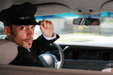 Fototapety Handsome male chauffeur sitting in a car saluting a viewer