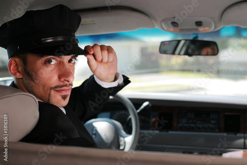 Handsome male chauffeur sitting in a car saluting a viewer