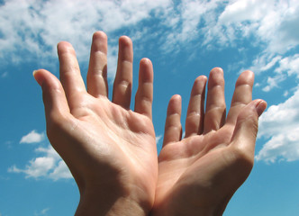 Praying hands by the sky