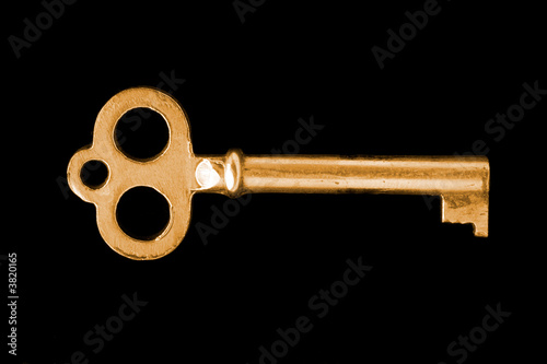close-up of gold vintage key isolated on black background