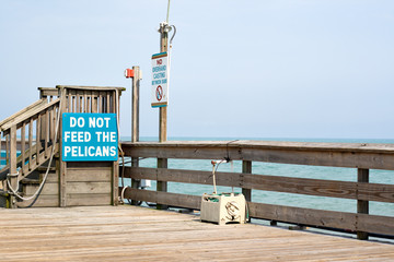signs on a rustic pier at Cocoa Beach, Florida