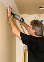 carpenter installing crown moulding in a home renovation