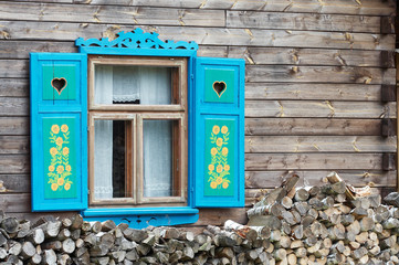 Opened window with decorative colorful shutters and logs below..