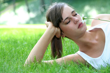 Young woman lying on lawn holding flower
