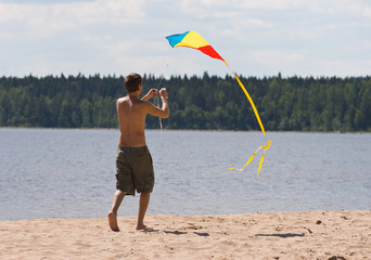 young man flying kite on a lake beach