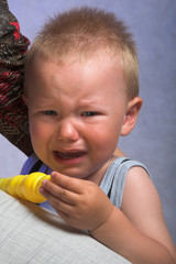 unhappy baby crying near the mother's hand