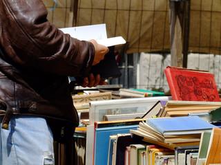 Mann beim Bücher lesen auf dem Flohmarkt
