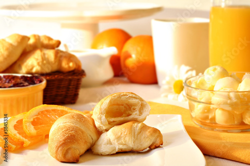 Fresh croissants with butter and jam, orange juice and coffee.