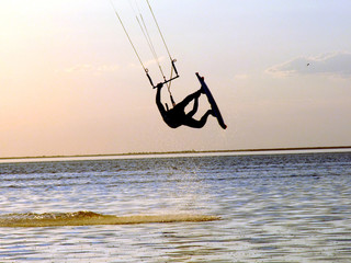 Silhouette of a kitesurf, a flying above water of a gulf